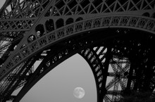 The Eiffel Tower and the full moon rising. B&W image.