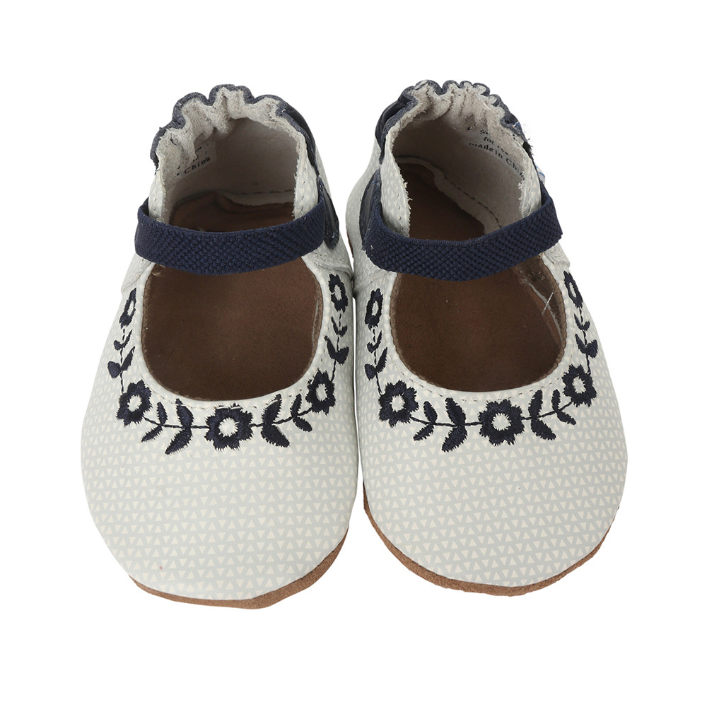 White leather baby shoes with black embroidered flowers.  These shoes fit infant girls or toddler girls age 0 - 2 years.