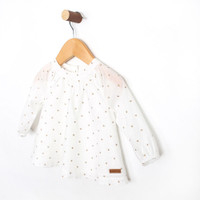 Baby girls shirt.  This white cotton top features a pattern of gold crowns.