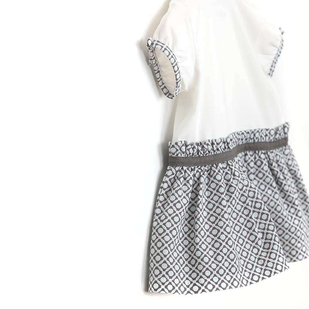Cotton dress with diaper cover for baby and toddler girls.  White top and aqua and grey geometric skirt. Detail View.