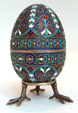"""The egg opens at the center and is marked with the silver quality mark """"84"""" on the interior of both halves along with a right facing kokoshnik and the delta symbol for the city of Moscow. The initials """"AAT""""  in Latin letters also appear on each half of the egg. These are the maker's marks for an unknown Russian silversmith. The stand  has the silver quality mark """"84"""". This piece is in excellent condition overall with no noted loss of enamel."""
