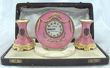 "Both the clock and candlesticks are marked with the name ""Faberge"" in Cyrilllic, the initials ""H.W."" for Henrik Wigstrom, the silver quality mark ""84,"" and a right facing kokoshnik with the alpha symbol representing the city of St. Petersburg."
