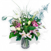 Light pink lilies, white calla lilies, white roses, aster and wax flowers arrangement