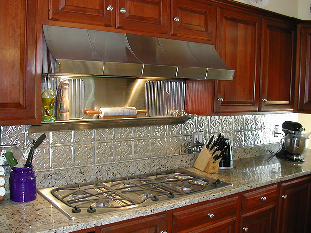Large Kithen With Wooden Cabinets, Stainless Steel Appliances And A  Matching Metal Backsplash.