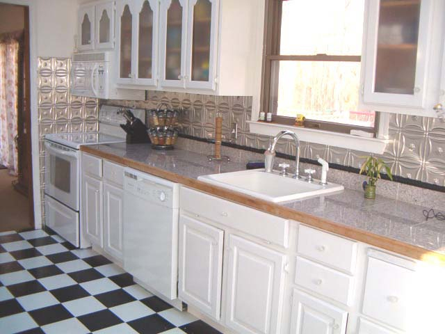 white cabinets with glass inserts metal backsplash and a checkered white and black flooring are - Kitchen Metal Backsplash