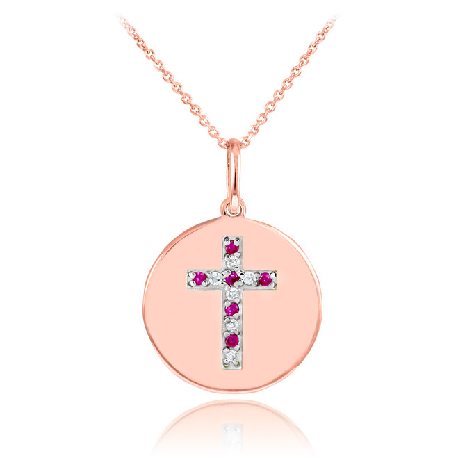 Cross disc pendant necklace with diamonds and rubies in 14k rose gold.