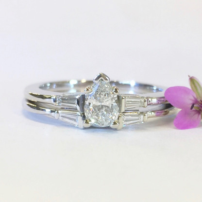 The PAMELA wedding set features a beautiful pear shaped diamond center and tapered baguette accents