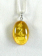 This seed syllable and a lotus flower is carved on the back of a yellow Amber disk.