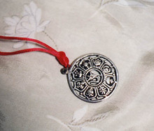 An OM Pendant, with the Eight Auspicious Symbols surrounding it. It is made from what they call 'white metal' and is very nicely done.