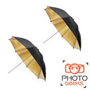 Two opened gold umbrellas showing their reflective inside and black outside.