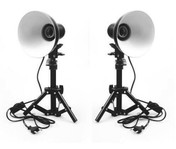 Two reflector tabletop lights facing forwards, connected to light stands.