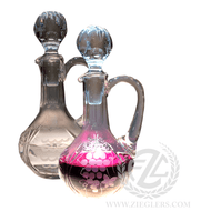 """This pair of glass cruets comes with a sandblast design. The water and wine cruet capacity is 5.5 OZ and come with glass stoppers to help keep the contents sealed.   Cruet Details: Glass Sandblast Design Stopper Top Cruets:  5.50 OZ Capacity 7.5"""" Height (w/stopper) Sold as a pair From Poland"""