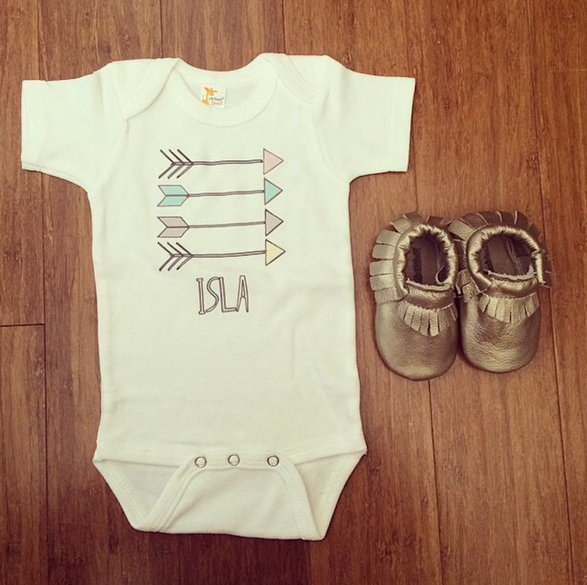 A customer photo of Isla's Aztec Arrows Baby Name Onesie (@caitlinlee94)