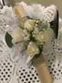 Spray roses, with babies breath, rhinestones, white ribbons and leaves.